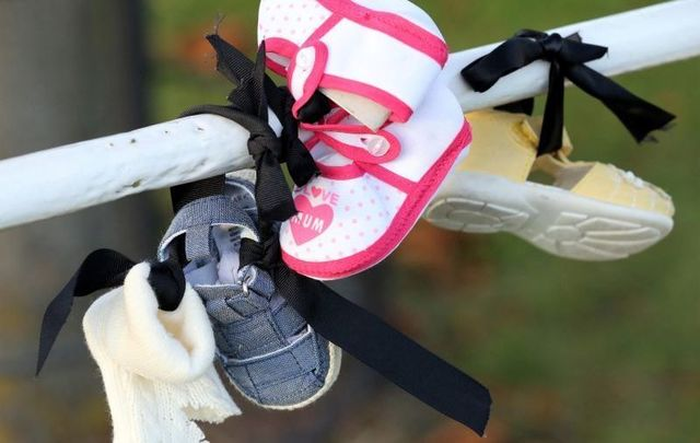 October 2020: Baby shoes hang from a railing at Aras an Uachtarain as part of a protest against calling on President Michael D.Higgins not to uphold the controversial Mother and Baby Homes legislation.