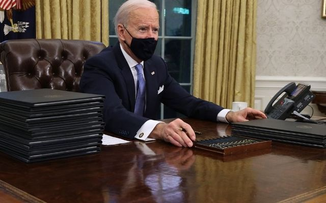 January 20, 2021: President Joe Biden signs a series of executive orders at the Resolute Desk in the Oval Office.