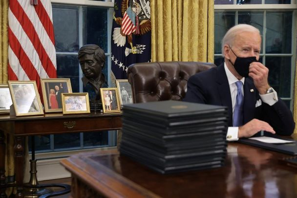 January 20, 2021: President Joe Biden in the Oval Office with a bust of Cesar Chavez in the background flanked by Biden family pictures.