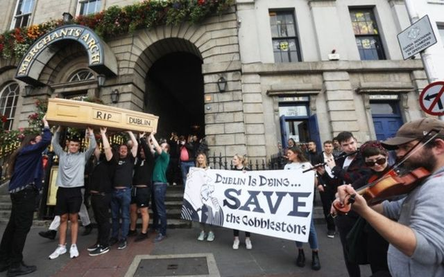 """Protesters carry a coffin with the words \""""RIP Dublin\"""" inscribed on it at Merchant\'s Arch in Temple Bar."""