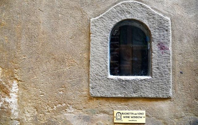 "Detail of an old ""buchetta del vino\"", a small window on the exterior wall of the ancient palaces used to sell wine to passers-by, Florence, Tuscany, Italy."