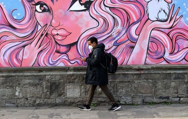 September 23, 2021: A person wearing a face mask passing a mural in Dublin City around the Grange Gorman Campus.