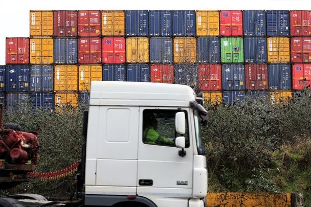 A truck passes cargo containers at Dublin Port on February 1, 2021.