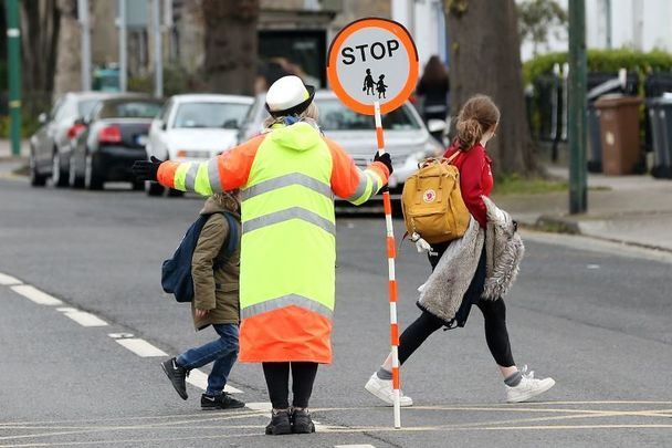 April 12, 2021: Children crossing the road with the help of traffic warden on their way to St Mathews National school in Sandyford, Dublin as all students return to school for the first time.