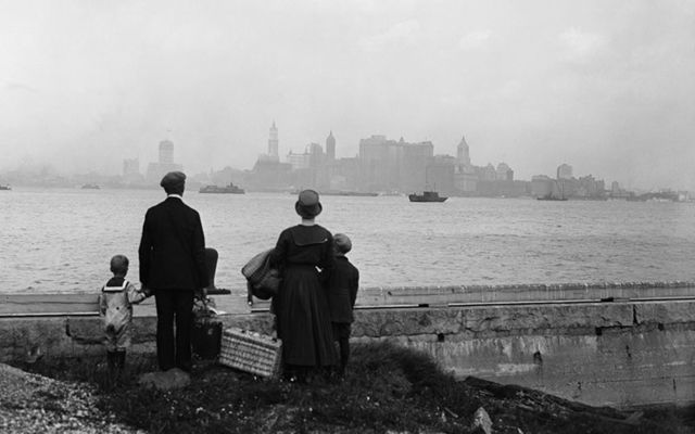 An immigrant family viewing New York City from Ellis Island, in 1925.