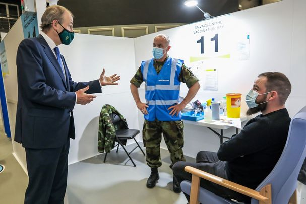 April 7, 2021: Taoiseach Micheal Martin speaking to vaccinator Tony O\'Sullivan from the Defence Forces and Jason Gleeson from Kilcock, as he visited the HSE Covid-19 Vaccination Centre in the Citywest Conference Centre in Dublin.