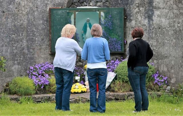 June 7, 2014: Members of the public pay their respects at the grounds where the unmarked mass grave containing the remains of nearly 800 infants who died at the Bon Secours mother-and-baby home in Tuam Co Galway from 1925-1961 rests.