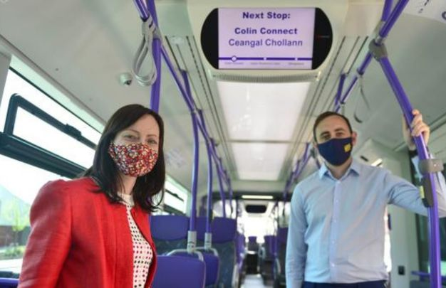 Northern Ireland\'s Infrastructure Minister Nichola Mallon and Piarais MacAlastair from Forbairt Feirste celebrate the launch of Irish language signs on West Belfast Gliders.