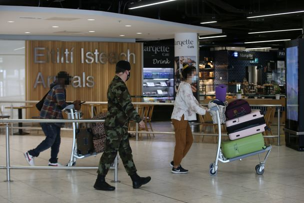 Military oversee arrivals at a quiet Dublin Airport.