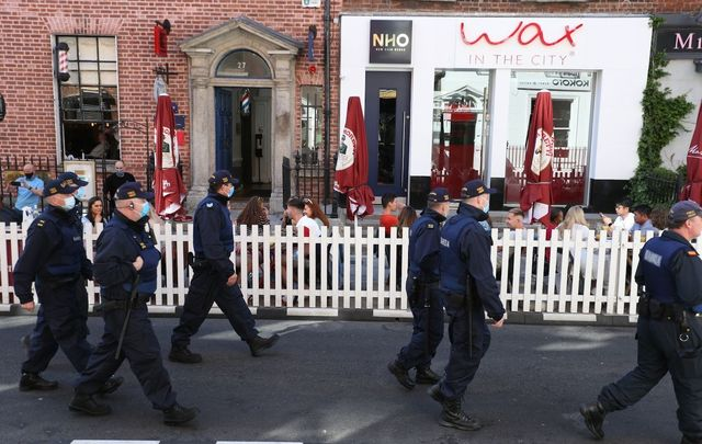 Police patrol South William Street, in Dublin City Center, as people enjoy outdoor dining during the fine weather.