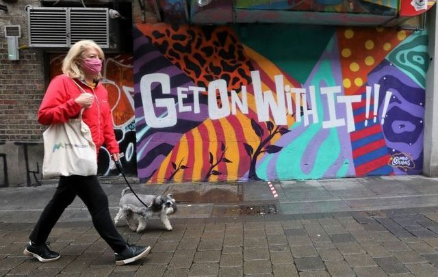 August 2020: A person wearing a face mask passes a mural that reads \'Get On With It\' in Dublin.