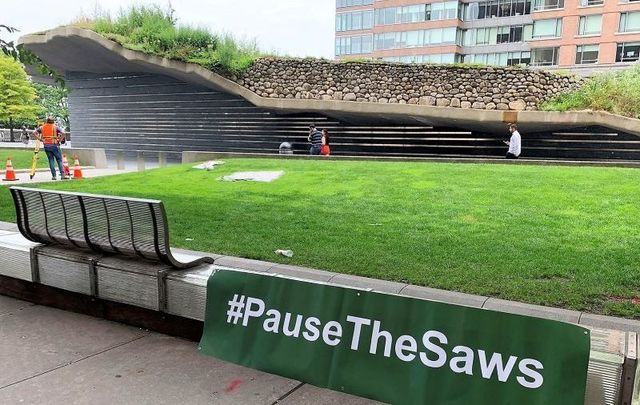 """July 8, 2021: A \""""Pause the Saws\"""" sign outside of the Irish Hunger Memorial in Battery Park, downtown Manhattan NYC."""