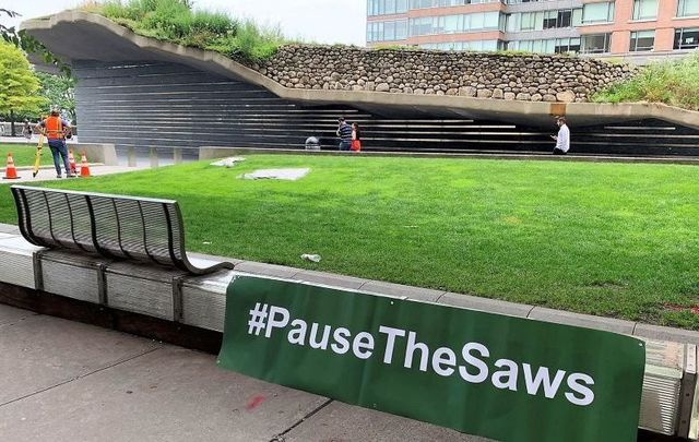 The Irish Hunger Memorial with a \'Pause the Saws\' sign.