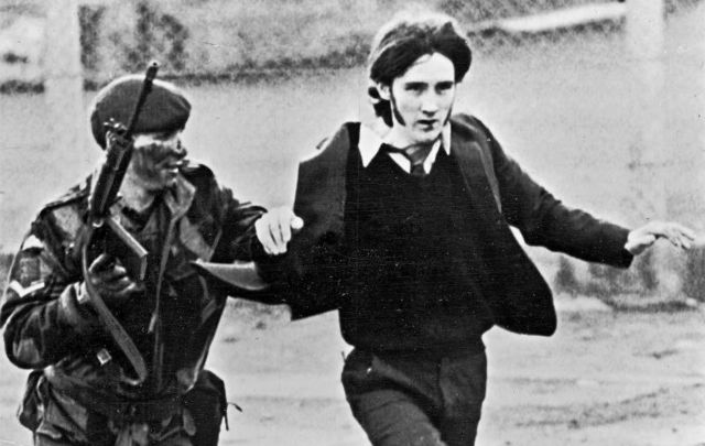 """January 30, 1972: A British paratrooper takes a captured youth from the crowd on \""""Bloody Sunday,\"""" when British paratroopers opened fire on a civil rights march, killing 14 civilians, in Derry."""