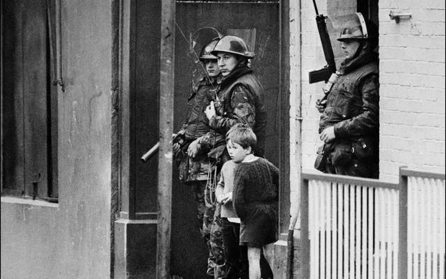 Children stand next to British soldiers during The Troubles in Northern Ireland.