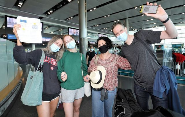July 19, 2021: Travelers at Dublin AIrport wearing face masks and holding their Covid Vaccine certs on the day that international travel returns for Ireland.