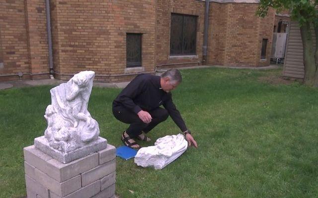 Father Miroslaw Podymniak examines the vandalism of a statue at St. Adalbert Church in Elmhurst, Queens.