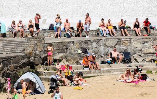July 21, 2021:  Members of the public enjoying the sun on Sandycove Beach.