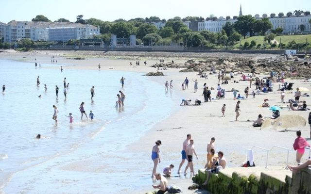 Crowds flock to Seapoint in Dublin during a period of fine summer weather. \n