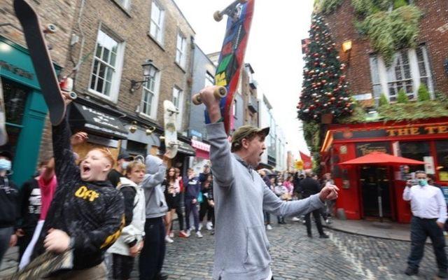 Protestors raise their skateboards outside the Temple Bar pub in Dublin.
