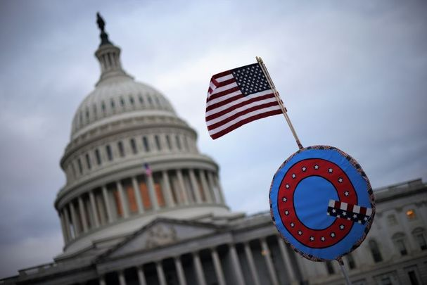 January 6, 2021:A U.S. flag with a symbol from the group QAnon as they gather outside the U.S. Capitol in Washington, DC.