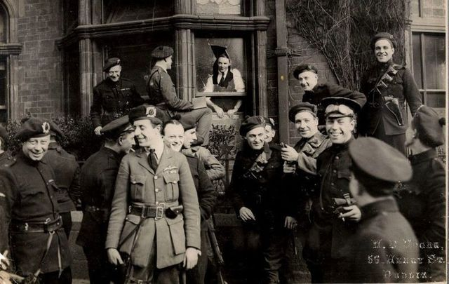 """April 11, 1921: This shot of joking Black and Tans and Auxiliaries was taken outside the London and North Western Hotel, North Wall, Dublin as they surveyed the damage after an IRA attack on their quarters. Written on the mount of this photo was \""""Tans glad to have escaped the bombs thrown at their headquarters in Dublin\""""."""