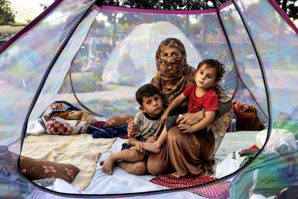 August 12, 2021: Farzia, 28, who lost her husband in Baghlan one week ago to fighting by the Taliban sits with her children, Subhan, 5, and Ismael, 2, in a tent at a makeshift IDP camp in Share-e-Naw park to various mosques and schools in Kabul, Afghanistan.