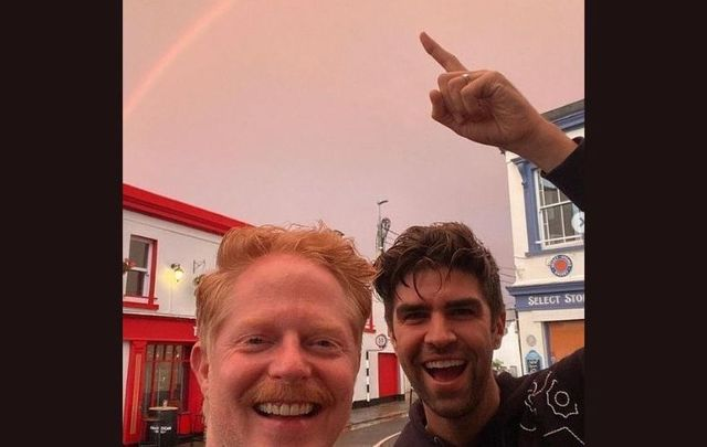 Jesse Tyler Ferguson and his husband Justin Mikita pose underneath a rainbow in Dalkey.