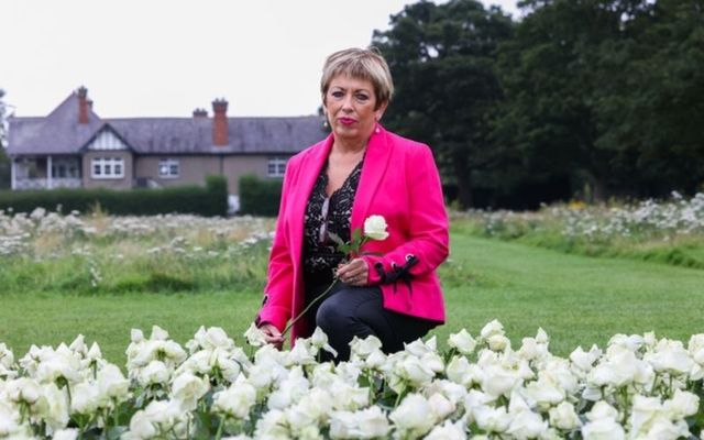 Eileen Finucane, whose partner Seamus died of COVID in April 2020, lays a white rose at the National War Memorial Gardens.