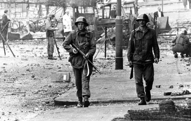August 16, 1969: British soldiers on patrol beside barbed wire defences at the junction of Percy Street and Falls Road in Belfast during unrest in Northern Ireland.