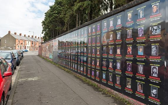 """A memorial wall along Beechmount Avenue in Belfast, dedicated to Catholics killed during the Troubles. A sign on the wall states that it is \""""dedicated to the families who have fought and are still fighting for truth and justice for their loved ones. It is also dedicated to all those who have died as a result of state-sponsored killings.\"""""""