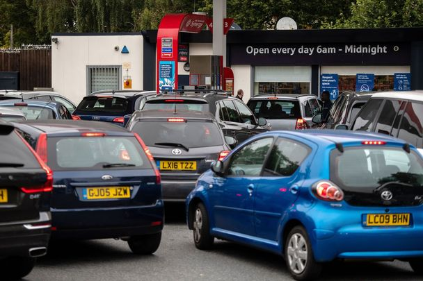 Cars line up outside a gas station in England.