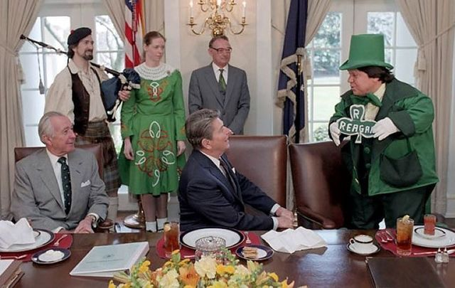 March 17, 1986: President Reagan and Don Regan celebrating St. Patrick\'s Day with a Leprechaun and Irish Dancer during an Issues Briefing Luncheon in the cabinet room.