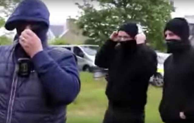 Unidentified men wearing balaclavas arrive at the eviction of a man from his home in Corofin, Co. Clare.