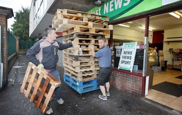 Sinn Féin's JJ Magee (right) and a member of the community removed wood from the New Lodge area