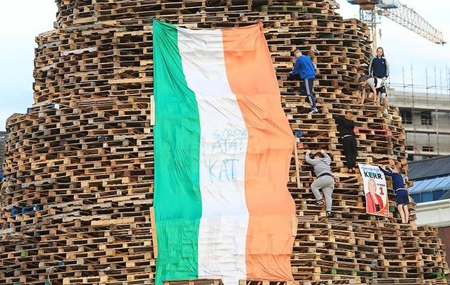 "Children climb a bonfire in Sandy Row south Belfast. The flag contains the letters ""KAT"" for ""Kill All Taigs,"" meaning Irish nationalists, and ""ATAT,"" meaning ""All Taigs Are Targets."""