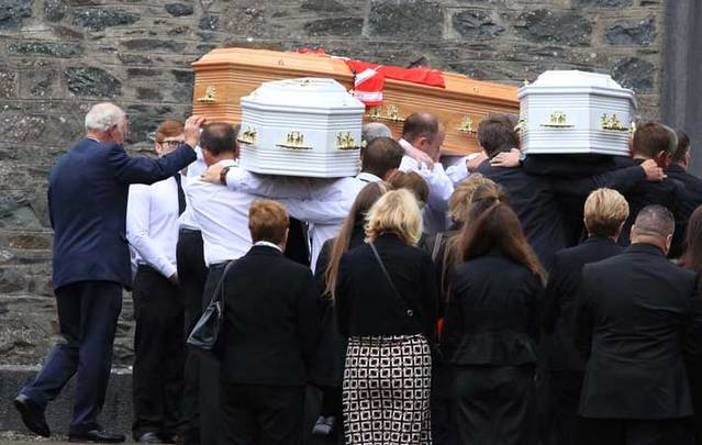 The bodies of the Hawe family arrive at the Church of St. Mary in Castlerahan in County Cavan. The photo shows the coffin of Alan Hawe, on the left, with his GAA club colors on top, and the coffins of two of his sons.