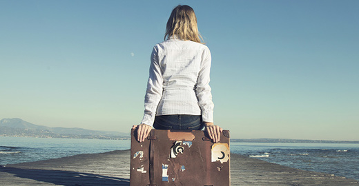 Cropped_mi_woman_suitcase_coast_pier_emigrant_immigration_travel_istock