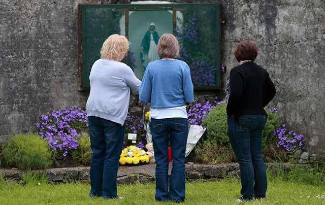 Women pay their respects at the grotto by the site of where 796 children from the Bon Secour Mother and Child home are believed to be buried.