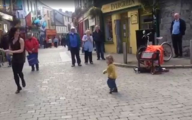 Two-year-old girl tries to copy the steps of an Irish dancer in Galway.