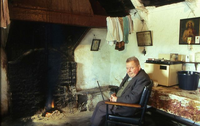 Tommy Cullen sits in front of his hearth in the family's traditional thatched cottage.