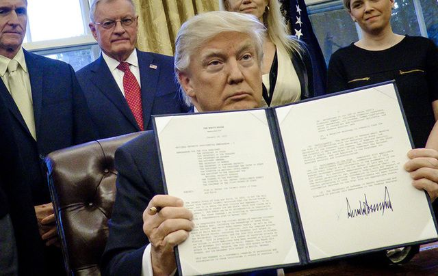 President Trump holds one of his executive orders in the Oval Office.