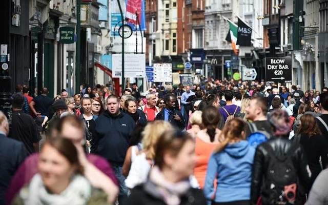 Crowds of people walk on Grafton Street in Dublin.