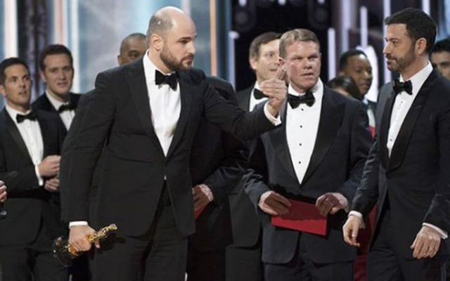Brian Cullinan (center) on stage as realization hits that Moonlight won Best Movie.