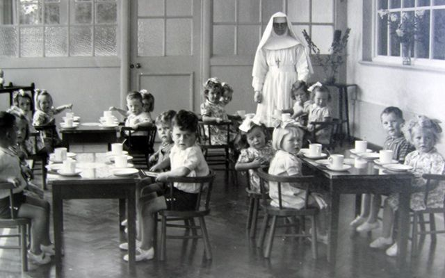 The horrors of Mother and Baby Homes. Children sit in a tea room with a nun posing for a photo.