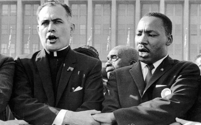 Father Ted Hesburgh singing with Martin Luther King Jr. during the Civil Rights fight.