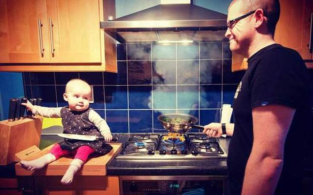 Photoshopped photo shows baby holding a knife near the stove as her dad looks on.