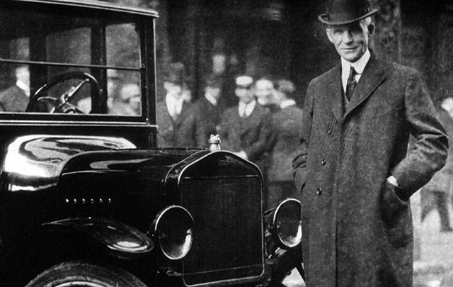 Proud of his Irish roots, Henry Ford, photographed with a model T Ford.