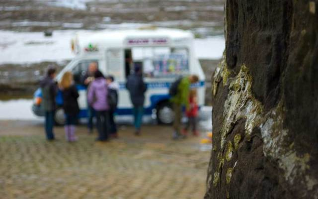 People buying ice cream from a van.