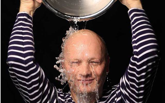 A man pours cold water over his head.